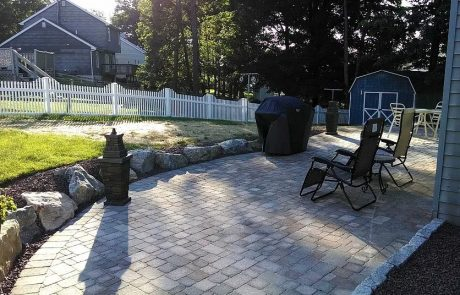 brick patio with grill and chairs